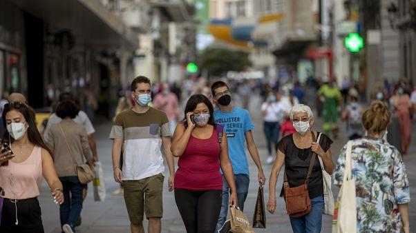 Personas con mascarilla caminan por una calle céntrica de Madrid