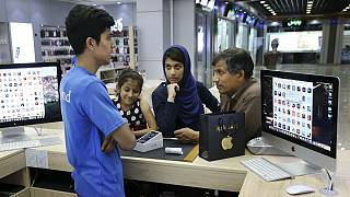 An Iranian shopkeeper talks to his costumers thinking of buying an iPhone in an electronics shop in Tehran, Iran