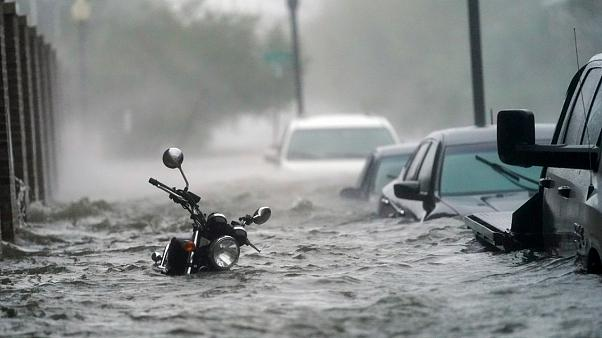 Cars and a motorcycle are underwater as water floods a street, in Pensacola, Fla., Wednesday, Sept. 16, 2020