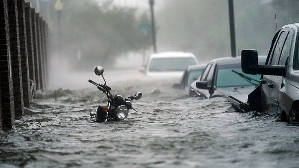 Cars and a motorcycle are underwater as water floods a street, Wednesday, Sept. 16, 2020, in Pensacola, Fla. Hurricane Sally made landfall Wednesday near Gulf Shores, Alabama.