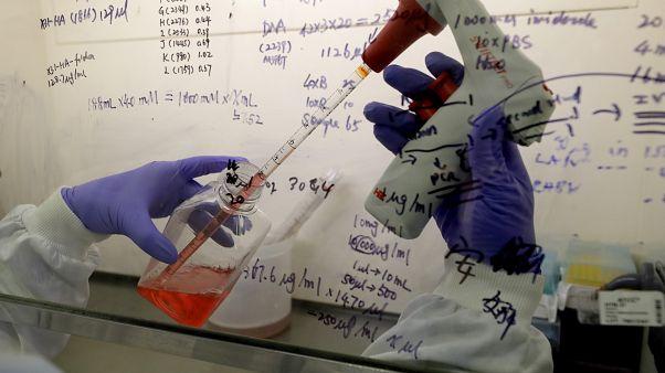 مختبر في جامعة إمبريال في لندن وعالم يعمل على تطوير لقاح كوفيد-19