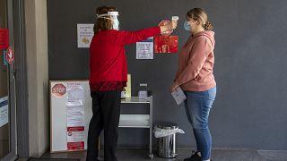 Una paciente se toma la temperatura en una clínica médica durante el confinamiento debido a la continua propagación del coronavirus en Melbourne, el jueves 6 de agosto de 2020