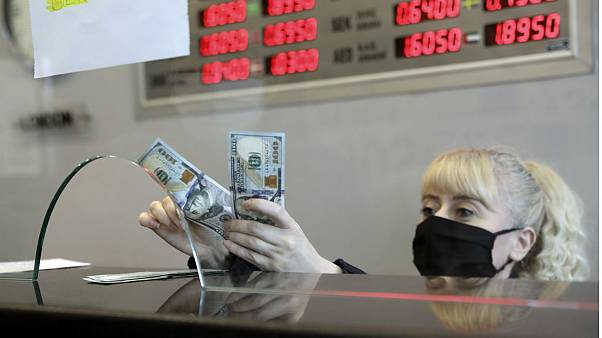 An official wearing a face mask for protection against the coronavirus, selling US dollar at a currency exchange office