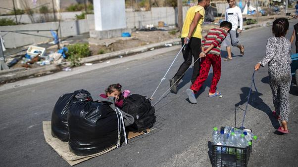 A child sits between plastic bags as migrants pull their belongings in Kara Tepe, near Mytilene the capital of the northeastern island of Lesbos, Greece