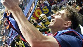In this June 6, 2015 file photo, Barcelona's Lionel Messi smiles to his mirror in the trophy after winning the Champions League final football match against Juventus.