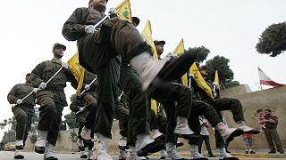 İsrail'le savaşta hayatını kaybeden Hizbullah üyeleri için kurulan yeni mezarın açılış töreninde yürüyen örgüt üyeleri (arşiv)