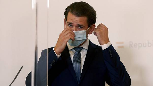 Austrian Chancellor Sebastian Kurz adjusts his face mask, standing behind two plexiglass shields during a press conference at the federal chancellery in Vienna, Austria