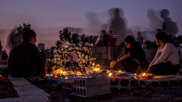 أقارب يزورون قبر في بلدة القامشلي شمال سوريا.
