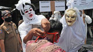 """""""Pocongnak"""", szellemnek öltözött rendőrök állítanak le egy motorost Tangerangban, és kötelezik a maszk viselésére"""