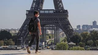 A man wearing a face mask as precaution against conoravirus walks at Trocadero plaza near Eiffel Tower in Paris.