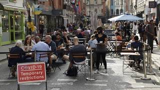People sit outside on a street closed to traffic to try to reduce the spread of coronavirus in London, Saturday, Sept. 19, 2020.