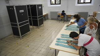 Volunteers stamp ballots at a polling station, in Rome, Saturday, Sept. 19, 2020.