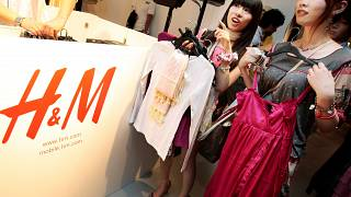 FILE: Shoppers on opening day of H&M's first Japan store in Tokyo's Ginza shopping district examine clothes, Sept. 13, 2008.