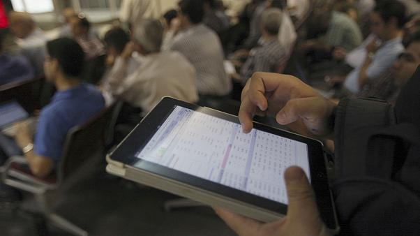 An Iranian shareholder monitors shares prices on his tablet at the Tehran Stock Exchange in Tehran, Iran