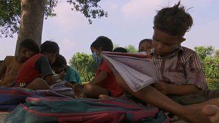 تلميذ يتلقى درسا على جانب أحد طرقات العاصمة الهندية