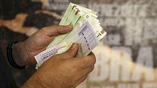A man counts his banknotes and traveler checks in Tehran, Iran