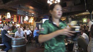 نادلة تقدم بيرة للعملاء في مطعم في دبي، الإمارات العربية المتحدة