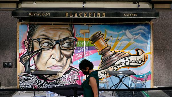 A mural in remembrance of Supreme Court Justice Ruth Bader Ginsburg covers plywood outside Blackfinn Ameripub, Monday, Sept. 21, 2020, in Washington.