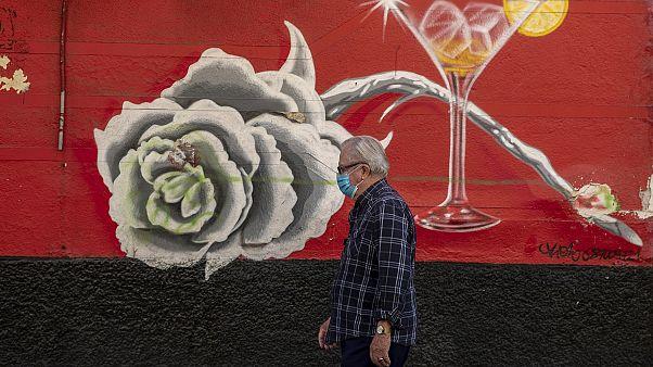 Un hombre con mascarilla pasea por la calle en el barrio madrileño de Usera