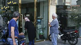 People wait in front of a closed money exchange shop for it to open, in downtown Tehran, Iran