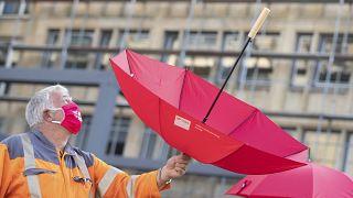 Esernyőt tart a magasba egy tiltakozó a németországi Güterslohban 2020. szeptember 22-én