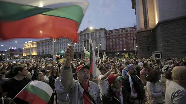 A protester shouts and holds the Bulgarian flag as protesters continue to demand the government's resignation.