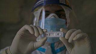 Un sanitario muestra el resultado positivo al coronavirus en Gauhati, India,  18 de septiembre de2020