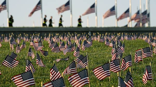 Activists from the COVID Memorial Project mark the deaths of 200,000 lives lost in the US to COVID-19 after placing thousands of small American flags in Washington DC.
