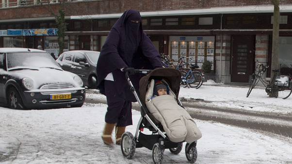 FILE - In this Monday Jan. 21, 2013 file photo, a woman wearing a full-face veil known as niqab, pushes a baby stroller on snow-covered streets in Amsterdam, Netherlands.