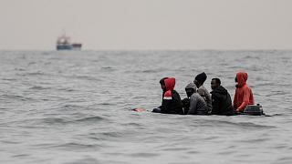 Migrants aboard a boat in rough waters in the English Channel as they attempt to cross to England