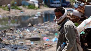 رجل يقف في شارع تغطيه النفايات في تعز وقد غمرته مياه المجاري المفتوحة. 2020/09/19