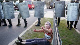 A woman reacts as she sits in front of law enforcement officers during a rally to protest against the presidential inauguration in Minsk on September 23, 2020.