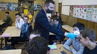 Преподаватель измеряет температуру ученику в московской школе.