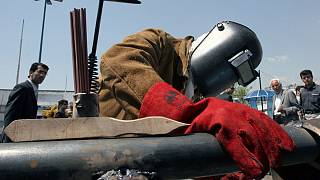 Iranian worker Amir Ghanbari welds a gas pipe in the Tehran's Oil, Gas, Petrochemical Show, Iran