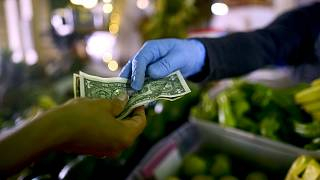 Owner of a fruit and vegetables stand, wears gloves as he exchanges cash with a customer