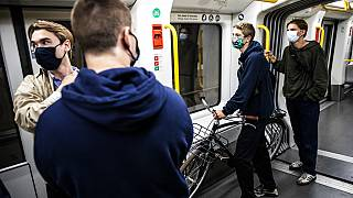 People wearing face masks ride a metro in Copenhagen, Denmark