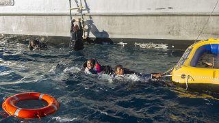 مهاجران يتعلقان بزورق مطاطي قبل أن تنقذهما فرق الطوارئ الإسبانية والبحرية المغربية قبالة الساحل الإسباني. 2012/12/03