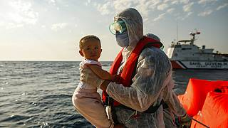 A Turkish coast guard officer, wearing protective gear to help prevent the spread of coronavirus, carries a child off a life raft during a rescue operation in the Aegean Sea,