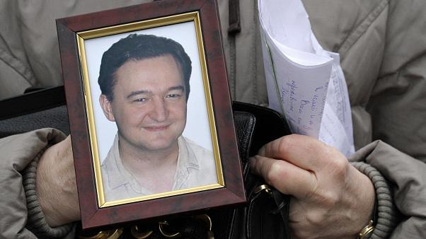 FILE - In this Nov. 30, 2009, file photo a portrait of lawyer Sergei Magnitsky, who died in jail, is held by his mother Nataliya Magnitskaya in Moscow