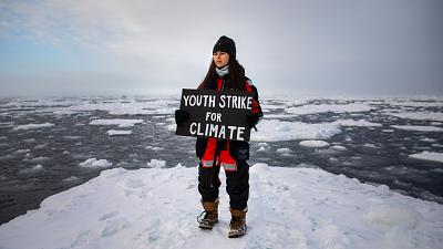 """British climate youth activist Mya-Rose Craig standing on ice floe holding a sign reading """"Youth Strike for Climate""""."""