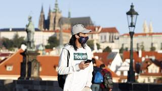 Maszkban sétáló fiatal Prágában