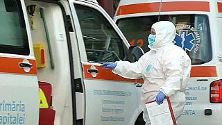 Un sanitario, equipado con un traje de protección, en Bucarest