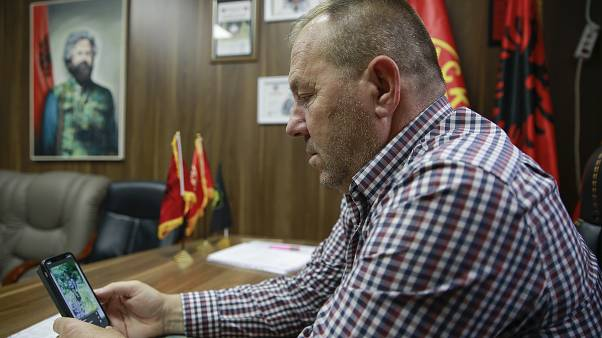 Hysni Gucati head of the War Veterans Organization of the Kosovo Liberation Army looks at a photo of former Kosovo Liberation Army commander Salih Mustafa after his arrest.