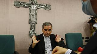 Angelo Becciu talks to journalists on Friday, a day after he resigned and renounced his rights as a cardinal