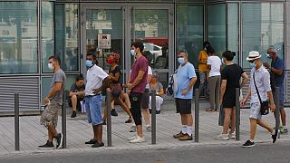 People wait in a line to get tested for COVID-19 outside a laboratory in Paris, Saturday, Aug 8, 2020.