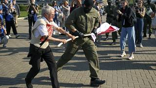 A police officer tries to take away an old Belarusian national flag from Nina Bahinskaya's hands during an opposition rally to protest the official election results.