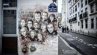 """Charlie Hebdo mizah dergisinin eski ofisinin bulunduğu sokakta 2015 yılındaki saldırıda hayatını kaybedenlerin karikatürleri """"Ben Charlie'yim"""" sloganı ile duvara çizili"""