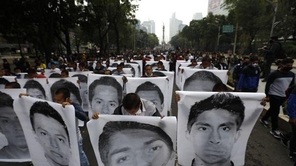 Estudiantes universitarios se manifiestan en Ciudad de México con carteles con los rostros de los estudiantes desaparecidos de Ayotzinapa