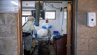 تطهير جثة قبل موكب جنازة في مشرحة خاصة بضحايا كوفيد-.19
