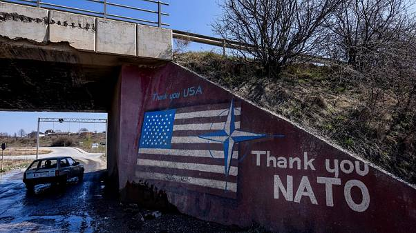 A car drives past a graffiti reading 'Thank You Nato' and featuring the US flag near the village of Stagovo on March 24, 2019.